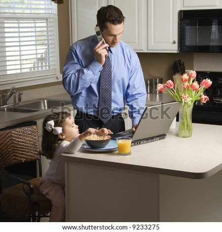 Caucasian father in suit talking on cellphone and using laptop computer with daughter eating breakfast in kitchen. - stock photo