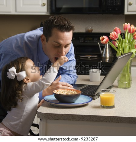 Caucasian father in suit using laptop computer with daughter feeding him breakfast in kitchen. - stock photo