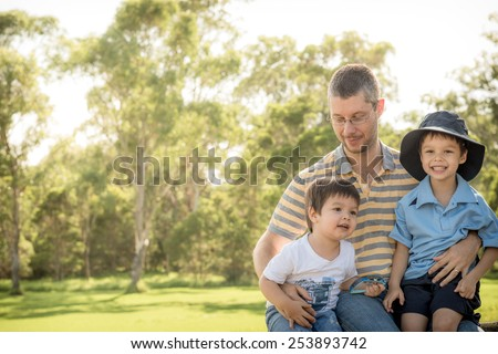 Caucasian father outdoors with his 2 mixed race Asian Caucasian sons on the older brother's first day of school - stock photo
