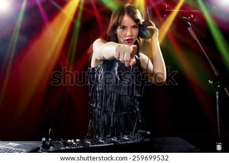 caucasian female dj using a mixer and computer to play mp3s - stock photo