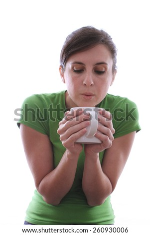 Caucasian female in green shirt is drinking a cup of coffee on an isloated background - stock photo