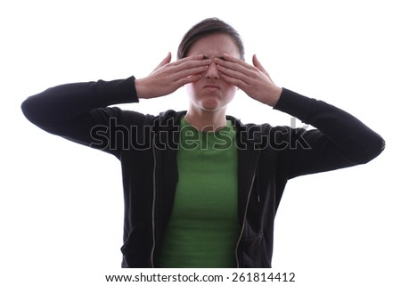 Caucasian female is hiding her eyes behind her hands. - stock photo