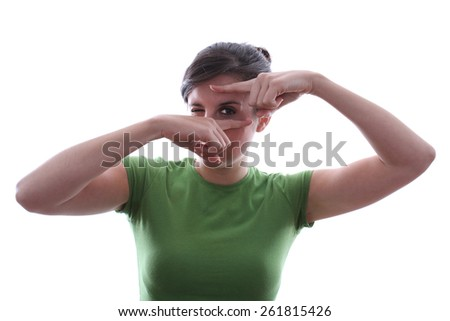 Caucasian female is looking at a subject through her fingers