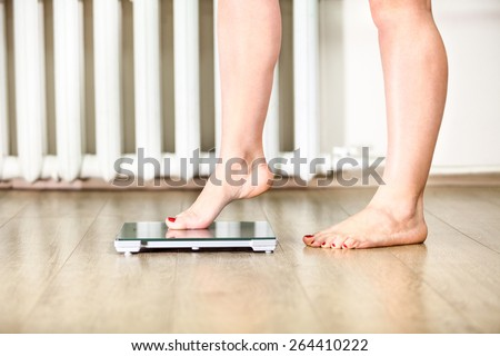 Caucasian female legs gently tread on the floor scales - stock photo