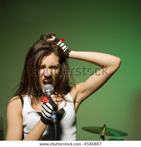 Caucasian female singing into microphone and pulling her hair. - stock photo