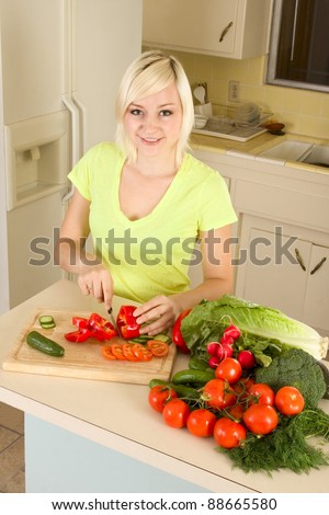 Caucasian female slicing tomatoes, cucumber and bell peppers on kitchen countertop