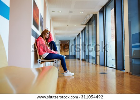 Caucasian female student sitting in the hallway interior at campus, college hipster girl sitting alone on the bench in university corridor, depressed teenager looking thoughtful and pensive  - stock photo