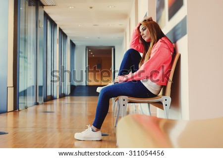 Caucasian female student sitting in the hallway interior at campus while  resting after long hard lessons, teenager girl waiting for someone while sitting on the bench in school corridor - stock photo