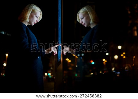 Caucasian female using automated teller machine with big digital screen while standing in night city out-of-focus lights, woman verifies account balance on banking application via modern device icon - stock photo