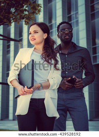 Caucasian female with laptop and black man posing over skyscraper.