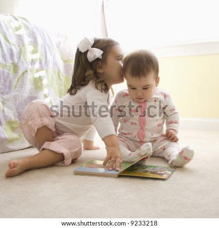 Caucasian girl children sitting on bedroom floor looking at book. [3.5 years old and 8 months old] - stock photo