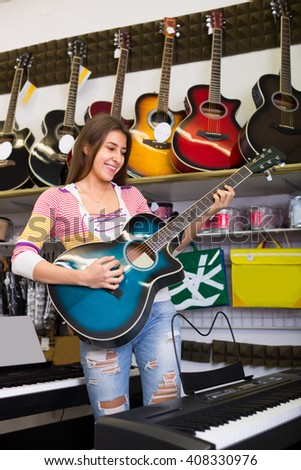 caucasian girl choosing acoustic guitar in music instruments shop