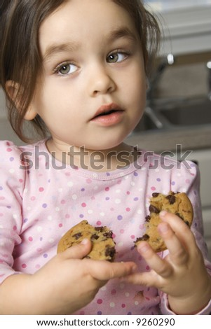 Caucasian girl eating chocolate chip cookie. - stock photo