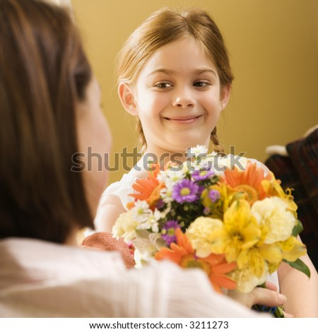 Caucasian girl giving mid adult mother flowers. - stock photo