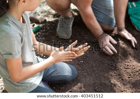 Caucasian girl kneels on soil and rub her hands - stock photo