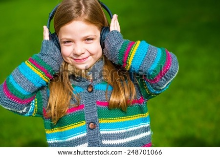 Caucasian Girl Listed Music Using Wireless Headphones. Girl Enjoying the Music. - stock photo