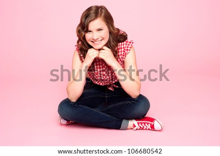 Caucasian girl sitting with hands on chin against pink background - stock photo