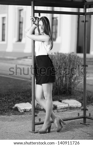 Caucasian girl waiting at old bus stop. - stock photo