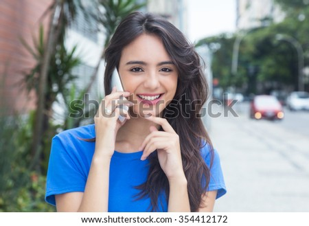 Caucasian girl with blue shirt laughing at phone in the city - stock photo