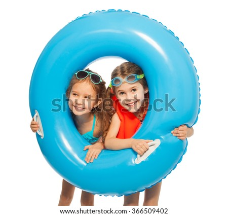 Caucasian girls looking out big blue rubber ring - stock photo