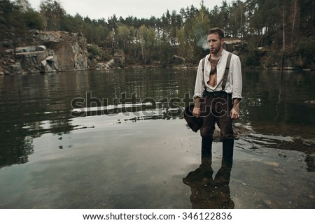 caucasian gold digger in retro clothes smokes cigarette while standing in lake with rocky bank after hard work. He wears shirt, leather pants, galluses and boots.  Sky is cloudy and grey.  - stock photo
