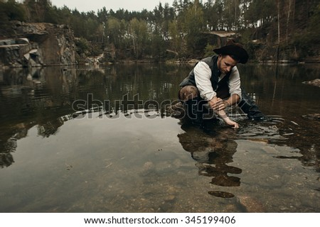 caucasian gold digger in retro clothes washes hands after hard work. He wears hat, shirt, leather pants, vest and boots. He sits on the rock in the water. Sky is cloudy and grey.