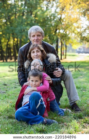 Caucasian grandparents walking with grandchildren in the autumn park - stock photo