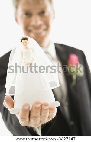 Caucasian groom holding out bride figurine in palm of his hand. - stock photo