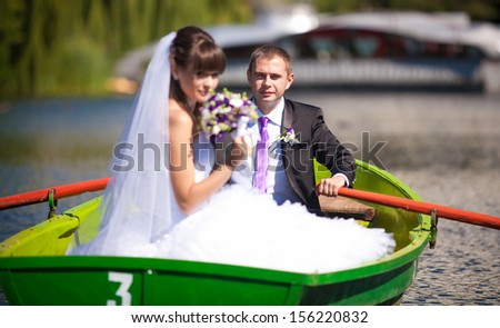 Caucasian groom rowing a boat while bride is holding flowers