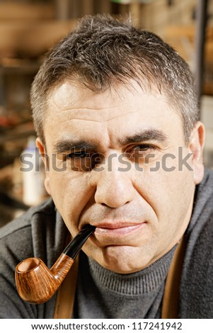 Caucasian guy smoking pipe in workshop - stock photo