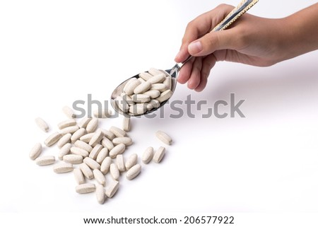 Caucasian hand holding spoon of supplements on white isolated background - stock photo