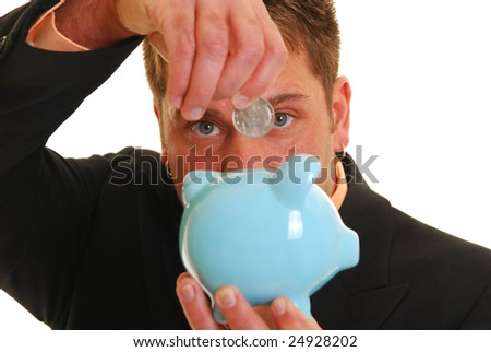 Caucasian hand putting a fifty cent piece into a piggy bank. Focus on eyes. - stock photo