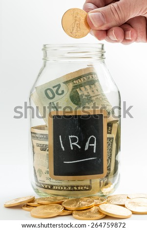 Caucasian hand putting gold coin into glass jar on white background with black chalk label or panel and used for saving US dollar bills for retirement in IRA precious metal fund - stock photo