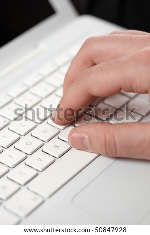 caucasian hand typing on a computer keyboard - stock photo