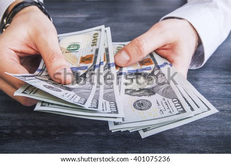 Caucasian hands counting dollar banknotes on dark wooden surface - stock photo