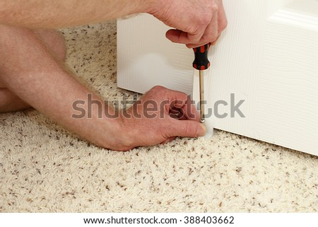 Caucasian hands of an adult male using a screwdriver to secure a white plastic closet door guide into a carpeted floor of a home. Securing a closet door floor guide