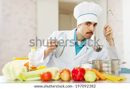 Caucasian handsome chef cooking soup with ladle  - stock photo