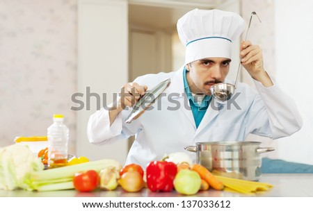 Caucasian handsome cook tasting veggie soup with ladle from pan in kitchen - stock photo