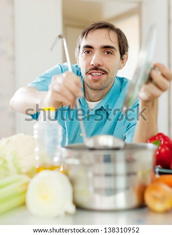 caucasian handsome guy with ladle cooking vegetables soup at kitchen - stock photo