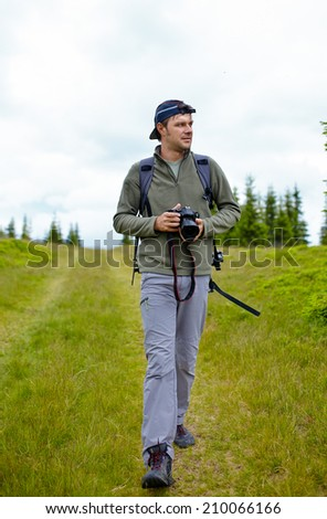 Caucasian hiker with camera on a pasture in the mountains - stock photo