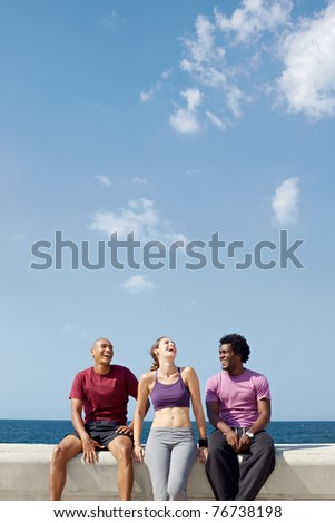 caucasian, hispanic and african american friends smiling and having fun near the sea. Vertical shape, three quarter length, copy space - stock photo