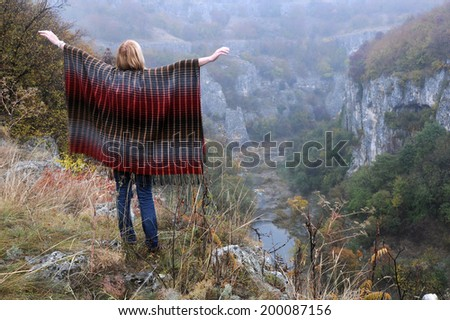 Caucasian lady stands on the edge of Emen canyon with her arms sideways near the city of Veliko Tarnovo in Bulgaria on a raw foggy morning in the fall - stock photo