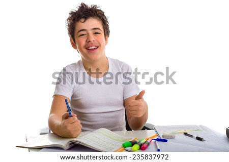 Caucasian Latin Teenager boy sitting while doing homework is happy and smiles showing his thumb finger to viewers as success sign and writing with pencil