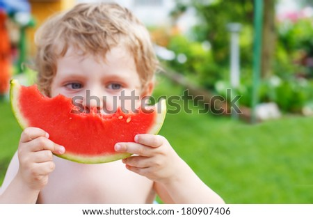 Caucasian little boy with blond hairs eating fresh watermelon in summer garden, outdoors.