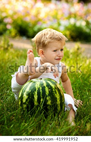 Caucasian little boy with blond hairs eating fresh watermelon in summer garden, outdoors. - stock photo