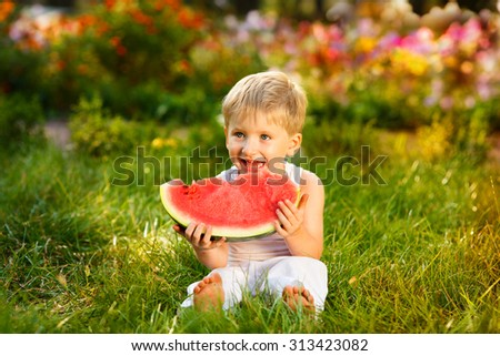 Caucasian little boy with blond hairs eating fresh watermelon in summer garden, outdoors.Kid eating red ripe watermelon - stock photo