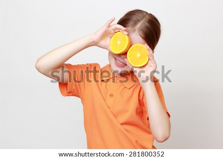 Caucasian little girl holding juicy oranges - stock photo