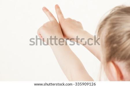 Caucasian little girl turning back and indicating something up, white background - stock photo