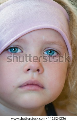 Caucasian little girl with blue eyes, curly blonde in a pink hat crying tears running down the face close-up - stock photo