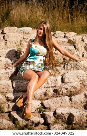 Caucasian long hair model in dress sitting on rocks. - stock photo